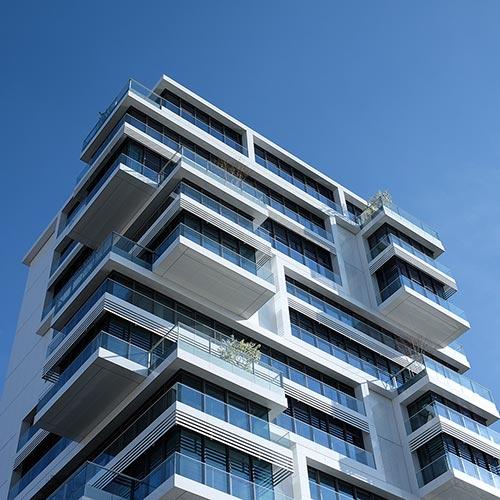 Ein modernes weißes Hochhaus mit vielen Wohnungen und Balkonen. Der Himmel ist strahlend blau